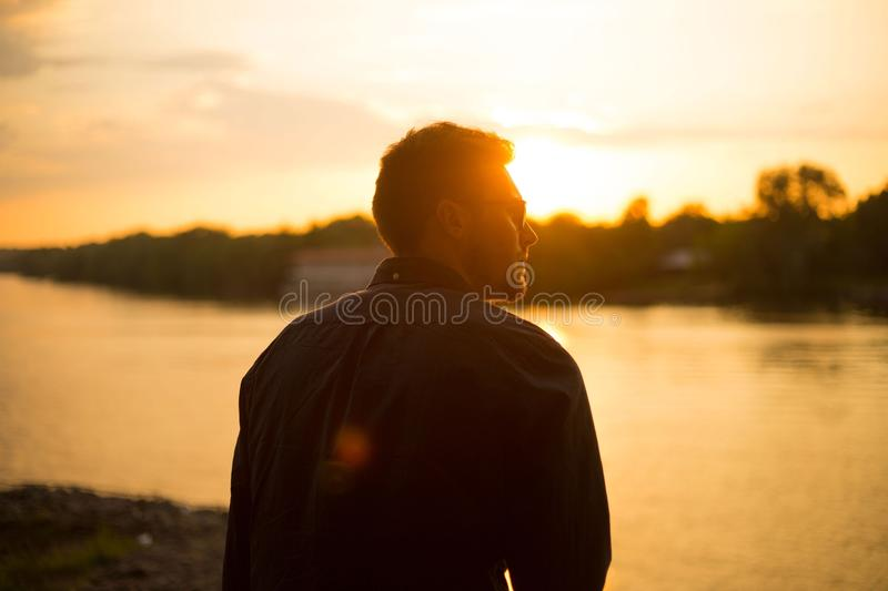 Man Sitting Near Large Body of Water Under Clear Sky during Sunset stock image
