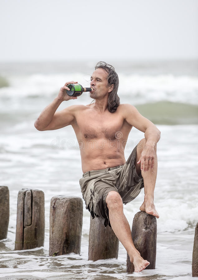 Man sitting near the sea and drinking alcohol royalty free stock photography