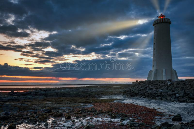 Man sitting next to Akranesviti lighthouse at night royalty free stock photo