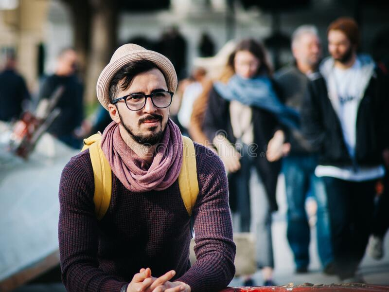 Man Sitting Next to Couple of Person Walking on the Street during Daytime stock photos