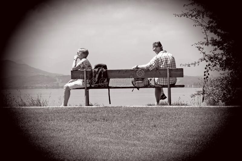 Man Sitting on Other Edge of Bench Parallel to Woman With Bags in Between Them stock images