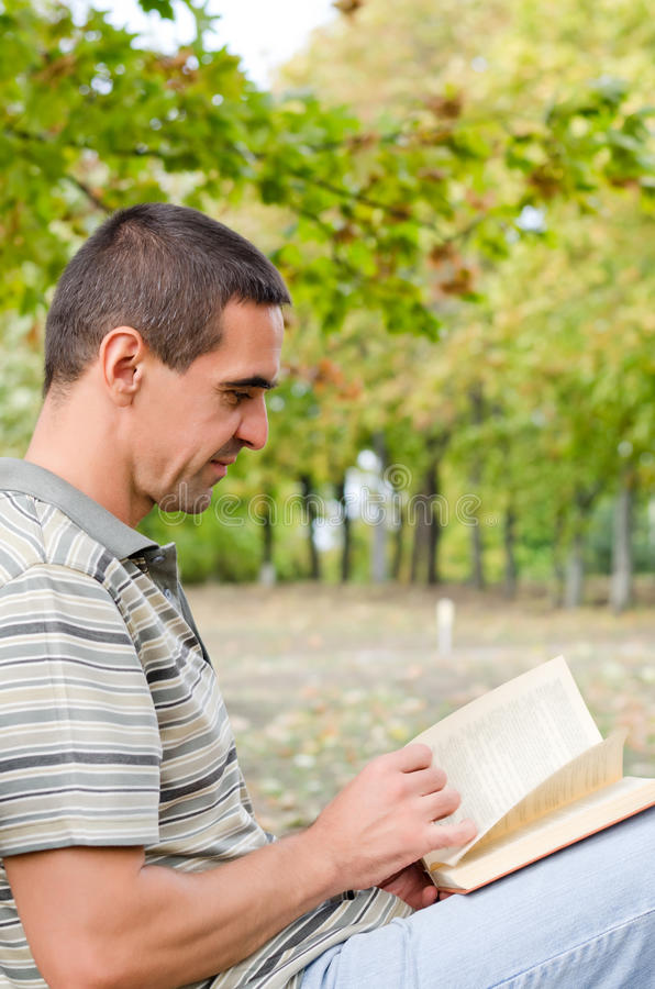 Download Man Sitting Outdoors Reading A Novel Stock Image - Image: 27241477