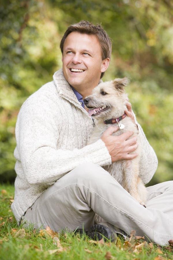 Man Sitting Outside Holding Dog Stock Photos