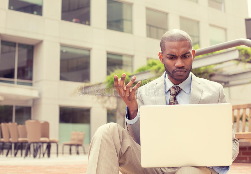 Man sitting outside office looking at laptop frustrated about computer crash royalty free stock photography