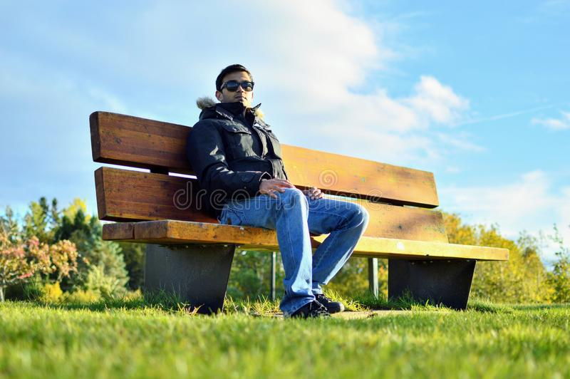 Man sitting in park stock photos