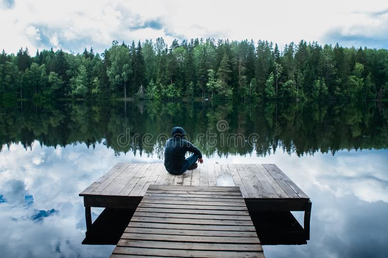 Man is sitting on the pier of a beautiful lake. The concept of freedom and independence, royalty free stock photography