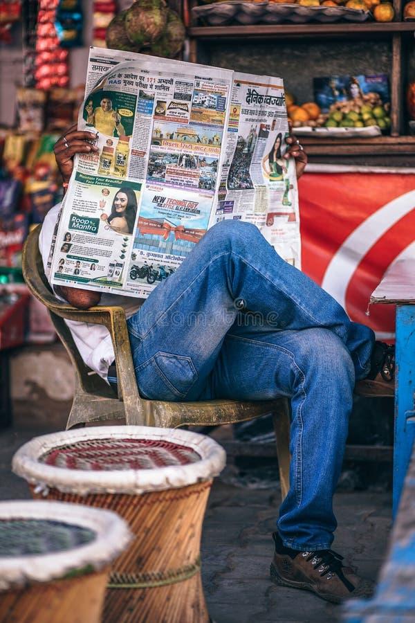Man Sitting on Plastic Armchair Reading Newspaper royalty free stock photo