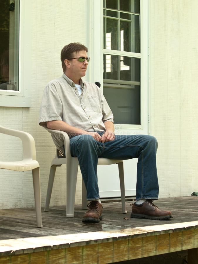 Man sitting on a porch. Man looking off into distance while sitting on a porch stock images