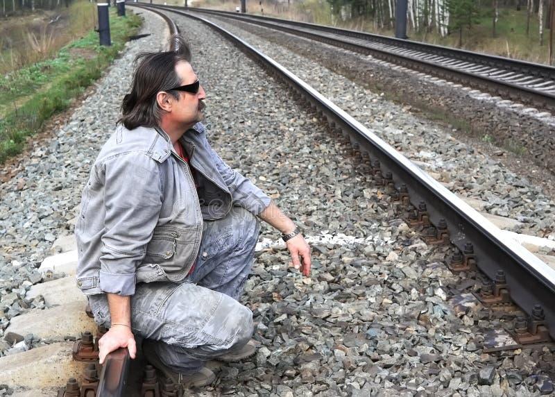 Download Man sitting on rail tracks stock photo. Image of away - 19224078