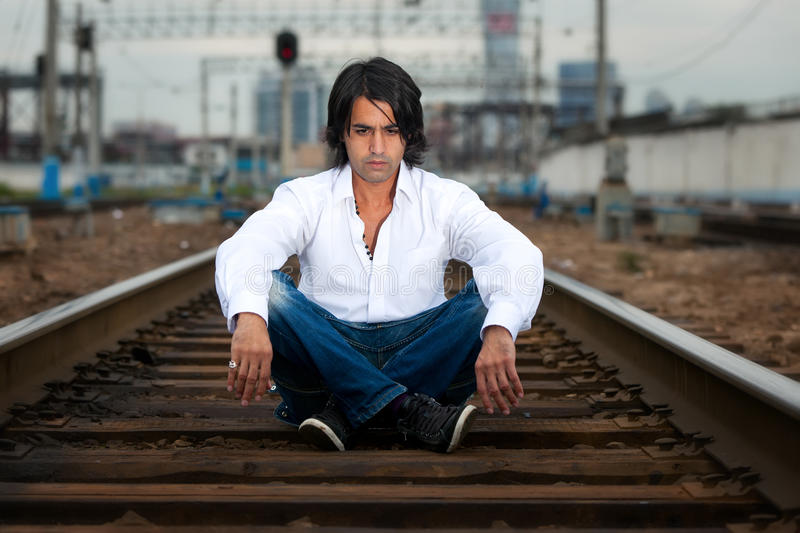 Man is sitting on the rails royalty free stock image