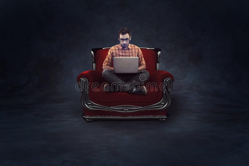 Man sitting on red armchair and using laptop. On a dark background royalty free stock images