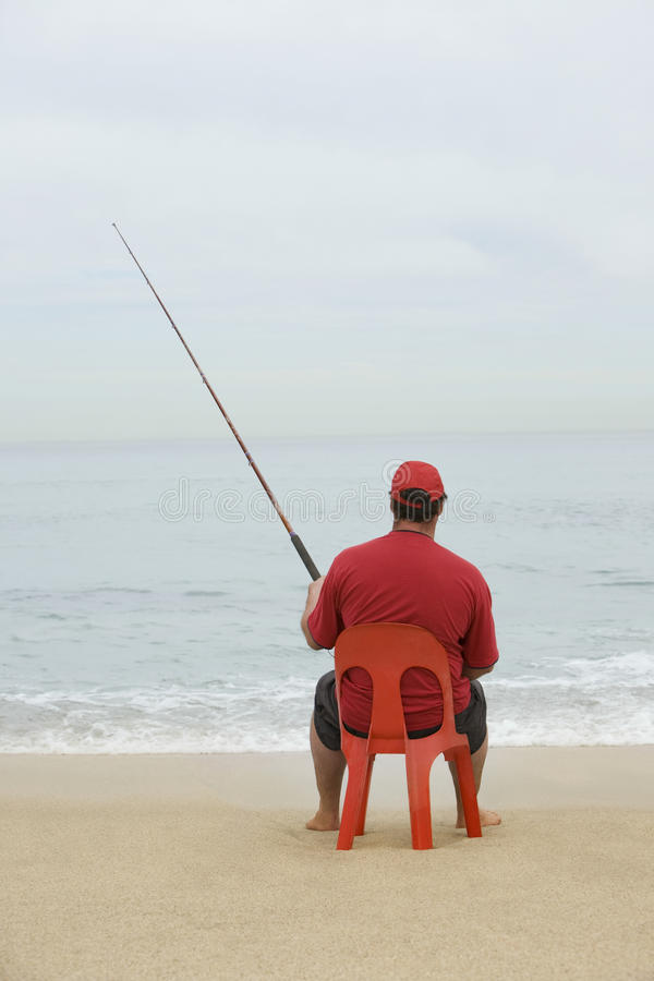 Man Sitting On Red Plastic Chair And Fishing At Beach royalty free stock images