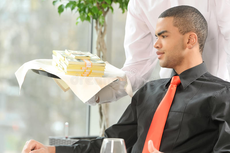 Man sitting in restaurant and looking at money. stock images
