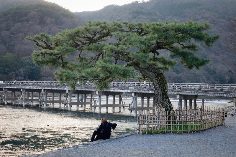 A man sitting on river bank in Kyoto, Japan royalty free stock image