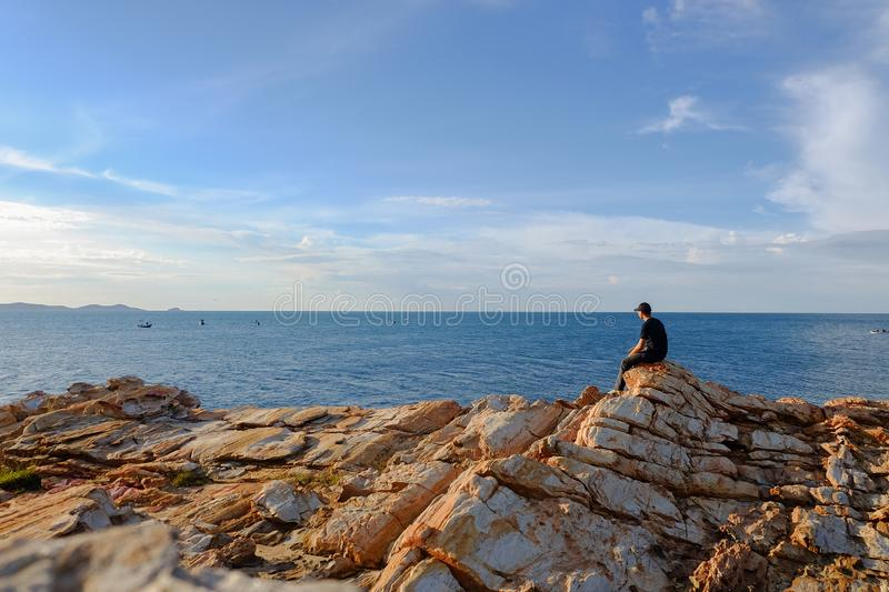 Man sitting on a rock. By the sea at Khao Laem Ya, Rayong, Thailand stock photography