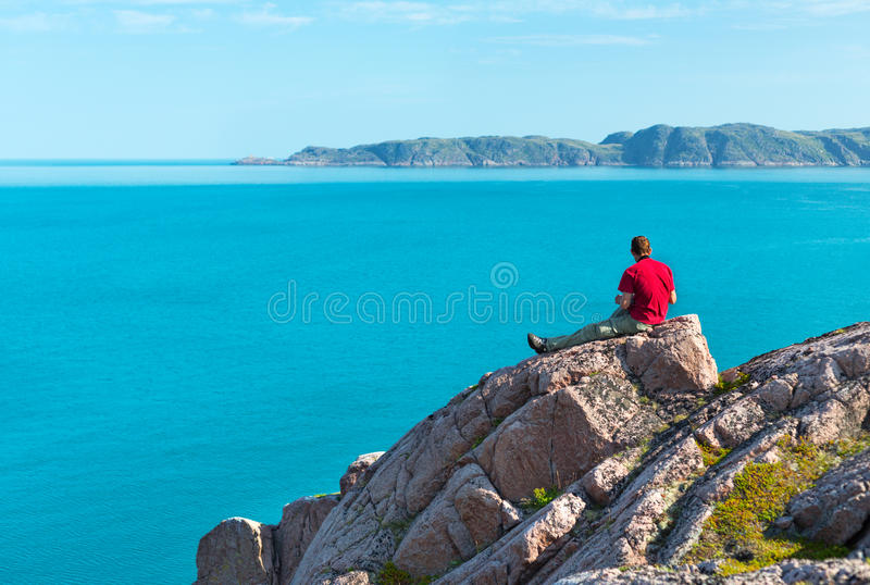 Man sitting on a rock stock photography