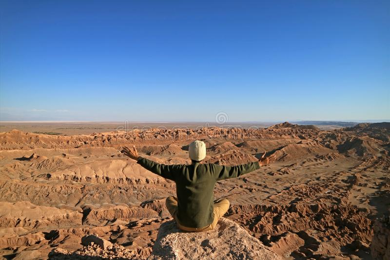 Man Sitting on the Rock Raising Arms Appreciating the Awesome view of the Moon Valley or Valle de la Luna royalty free stock photo