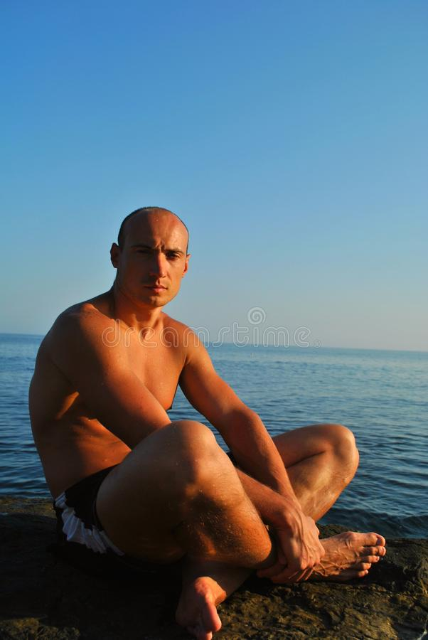 Man sitting on a rock at the sea royalty free stock photography
