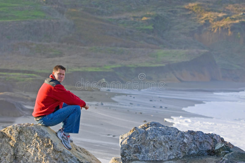Man Sitting on Rocky Beach royalty free stock photos