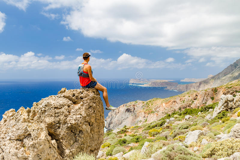 Man sitting on rocky ledge, Crete Island, Greece. Man sitting on rocky ledge overlooking Mediterranean Sea on Crete Island, Greece stock images