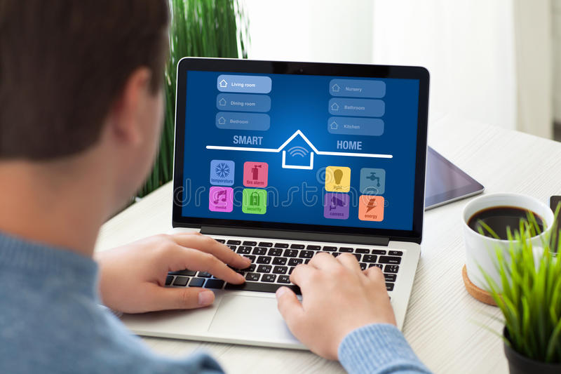 Man sitting in room with notebook app smart home screen. Man sitting in the room with notebook app smart home on screen royalty free stock images