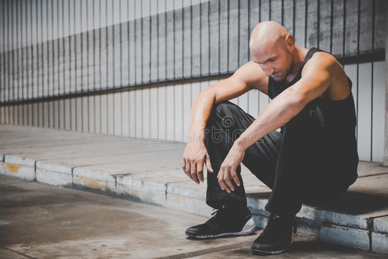 Man Sitting on Sidewalk royalty free stock photography