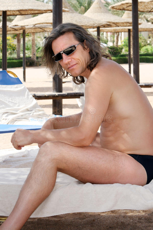Man sitting sideways on the beach with sunglasses stock images