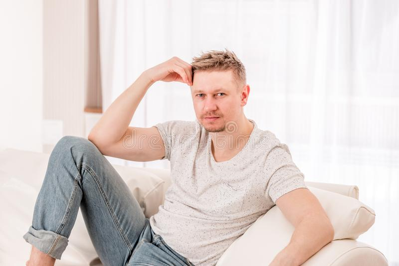 Man sitting at the sofa in bedroom stock images