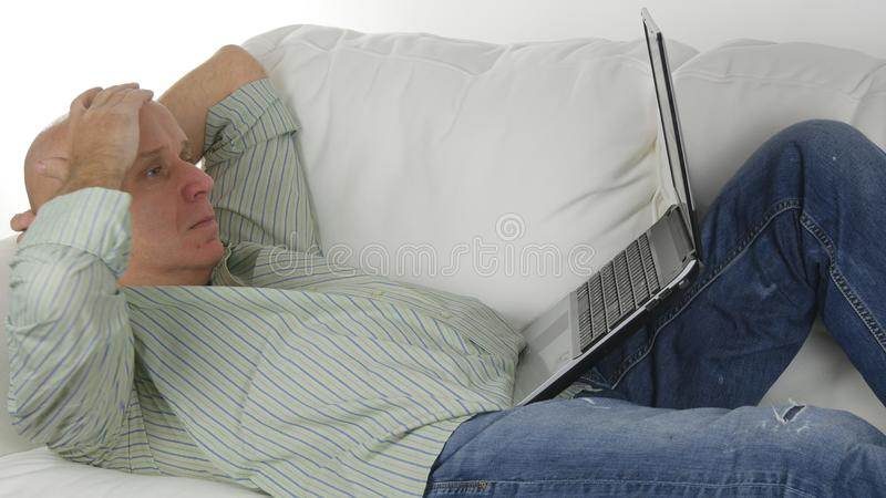 Man Sitting on the Sofa Doing Business Using Laptop Make Disappointed Gestures stock photography