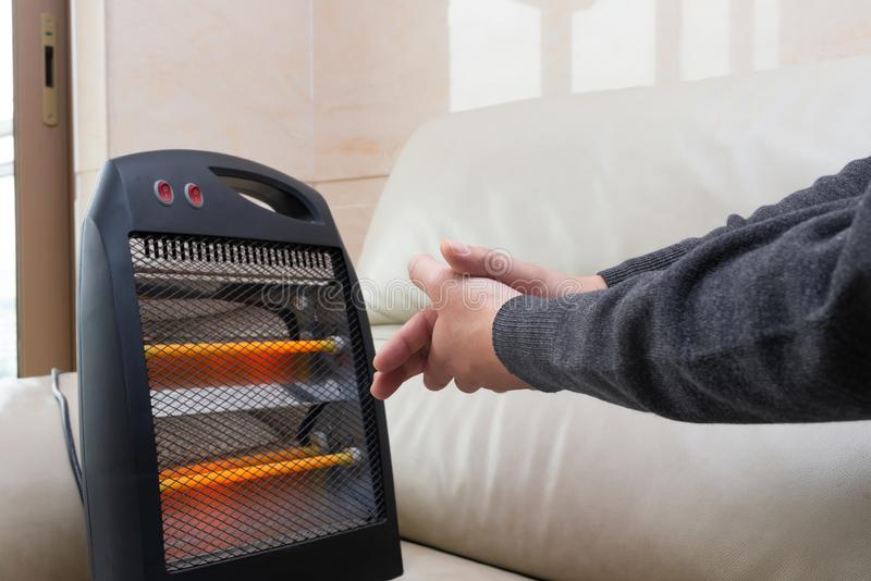 Man sitting on sofa with electric heater near his hands stock photo