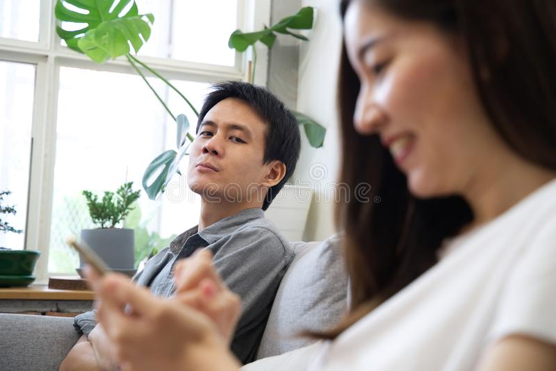 A Man sitting on sofa is feeling unhappy with his girlfriend. royalty free stock photos