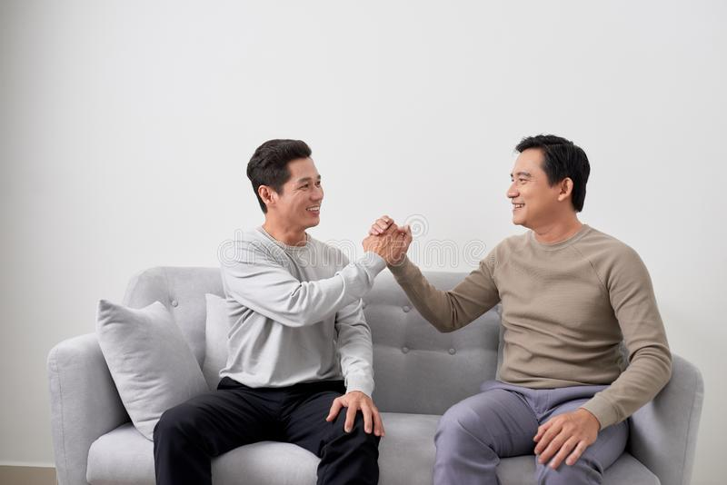 Man sitting on sofa and handshaking with friend at home. Multiracial people friendship stock photography
