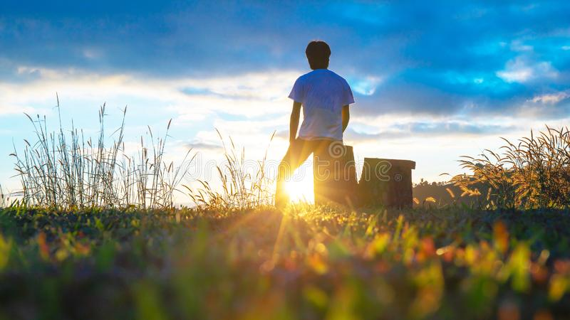Man sitting or standing on the mountain with sunset or evening time with sun light sunbeam or sunray. People background royalty free stock photography
