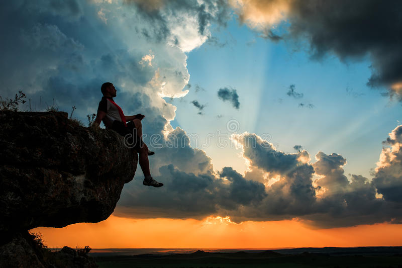 Man sitting on stone top of high mountain. On the sunset royalty free stock image