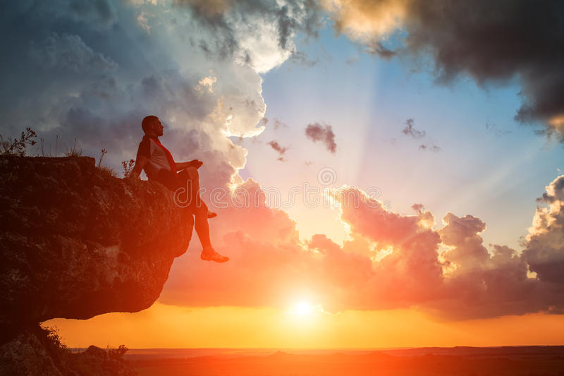 Man sitting on stone top of high mountain. On the sunset stock photos