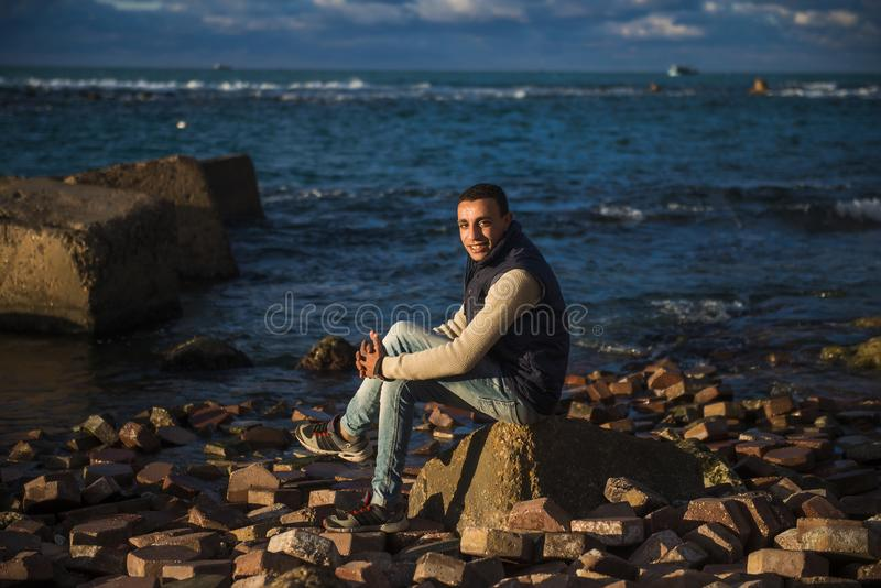 Man Sitting on Stone Under the Blue Sky stock photography