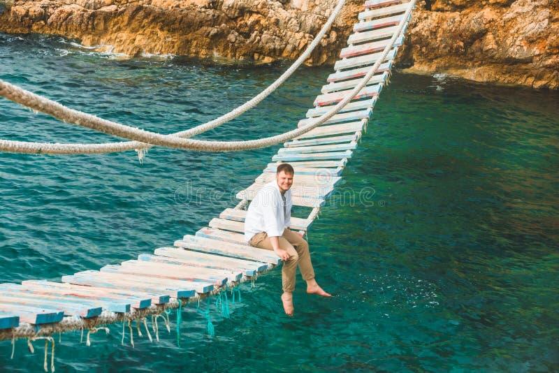 Man sitting at suspension bridge enjoying sea view and nature calmness stock images