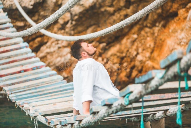 Man sitting at suspension bridge enjoying sea view and nature calmness stock photo