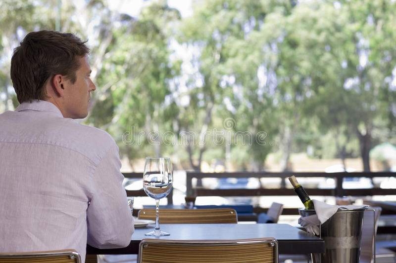 Man sitting at table on restaurant balcony with glass of wine and ice bucket, rear view royalty free stock images