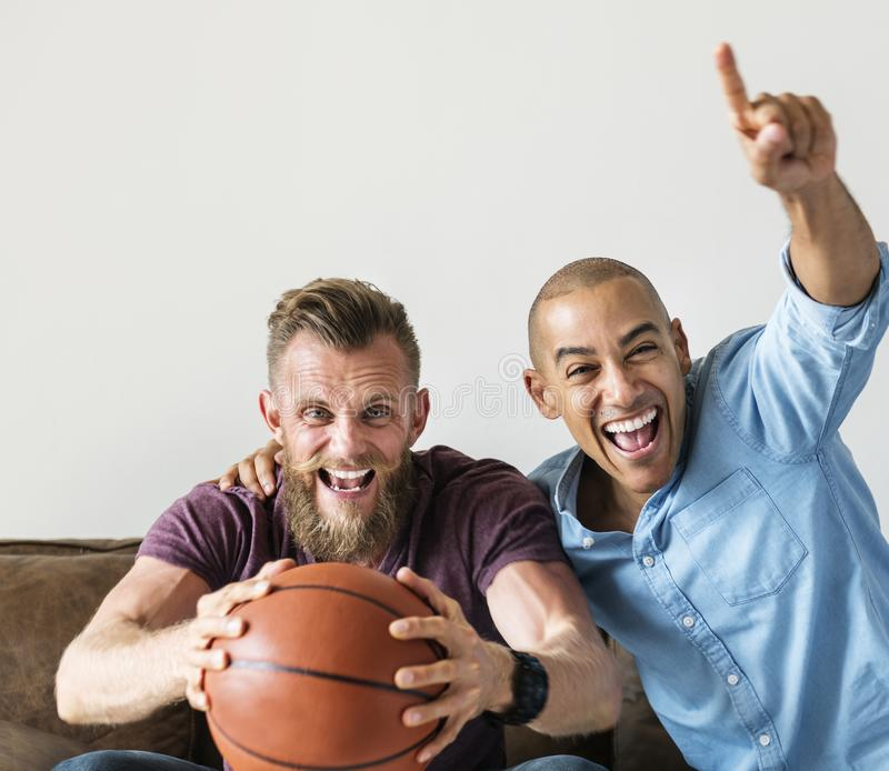 Man sitting together on a couch watching sport stock photography
