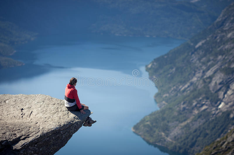 Man sitting on trolltunga rock in norway. Above lake stock photography