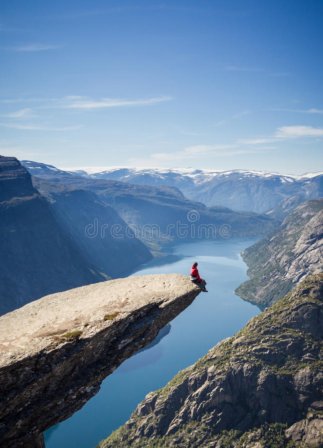 Man sitting on trolltunga rock in norway. Above lake royalty free stock photos