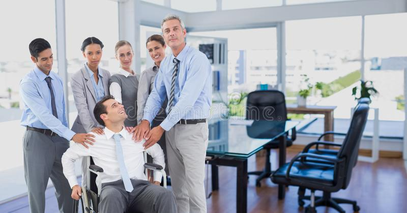 Man sitting in wheelchair and colleagues standing beside him royalty free stock photography