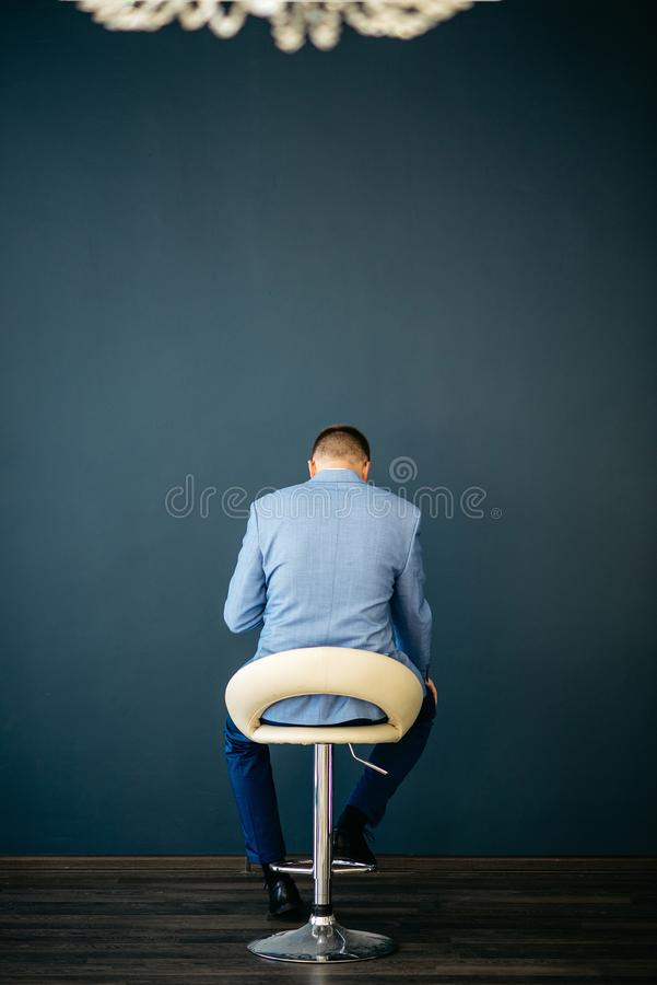 A man is sitting in a white chair against a blue wall. View from the back. A man is sitting in a white chair against a blue wall. He bowed his head and thought stock photography