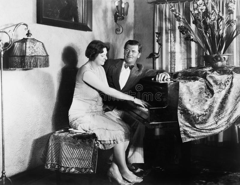 Man sitting with woman playing the piano. (All persons depicted are no longer living and no estate exists. Supplier grants that there will be no model release royalty free stock images