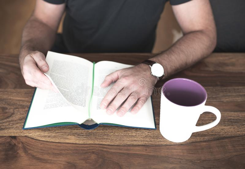 Man sitting at wooden table reading a book stock photos