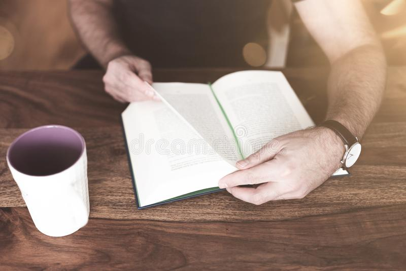 Man sitting at wooden table reading a book stock photo