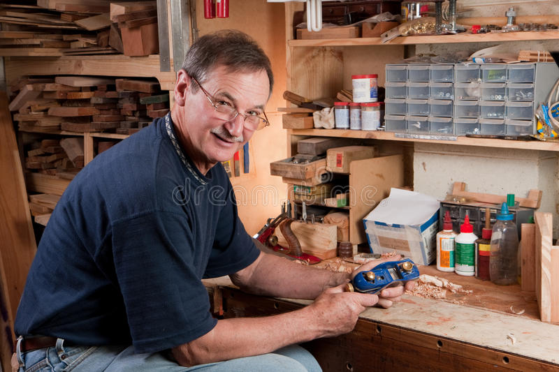 Download Man Sitting At Workbench In Workshop Stock Photo - Image: 17070330