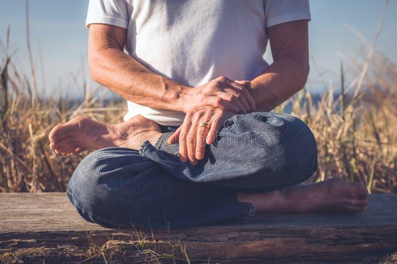 Man sitting in yoga pose. stock image. Image of serenity