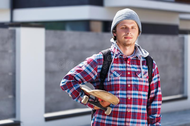 Man with Skateboard. Hipster man dressed in cheked shirt and cap holding skateboard before grey fence, outdoor street portrait royalty free stock photography